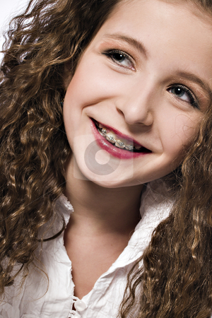 Young girl with braces stock photo, Studio portrait of a young curly haired girl with braces by Frenk and Danielle Kaufmann