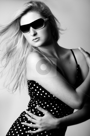 Girl with sunglasses looking down stock photo, Beautiful girl with a pair off sunglasses in the studio by Frenk and Danielle Kaufmann