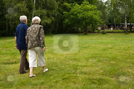 Older couple walking through a park stock photo, Outside portrait of an elderly couple in a park by Frenk and Danielle Kaufmann