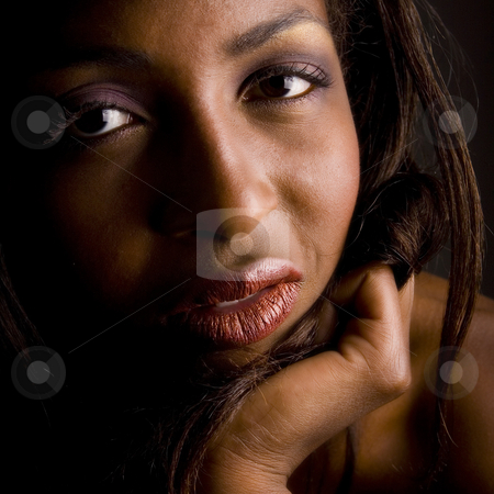 Dark female model looking interested stock photo, A beauty portrait taken from an african model in the studio looking interested by Frenk and Danielle Kaufmann