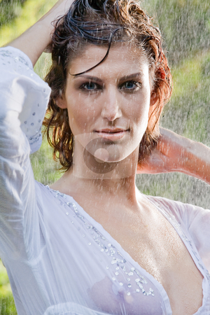 Brunette in white blouse standing in the rain stock photo, Brunette in see through blouse standing in the rain by Frenk and Danielle Kaufmann