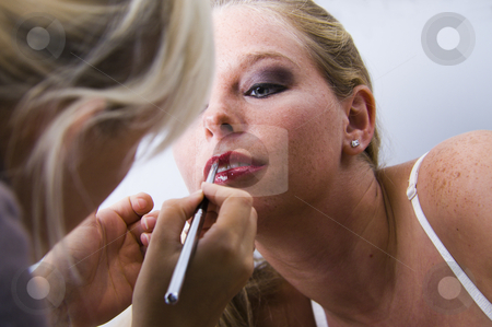 Model getting her lipstick done stock photo, Studio portrait of a beautyfull blond model getting her lipstick applied by Frenk and Danielle Kaufmann
