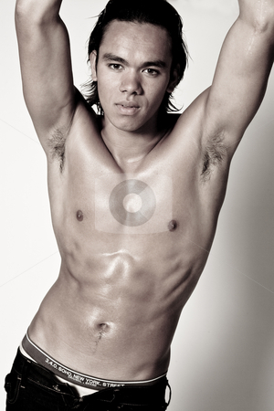 Asian sexy looking boy showing his muscles stock photo, Studio portrait of a muscular Asian sexy looking boy by Frenk and Danielle Kaufmann