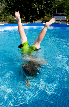 Boy Swimming stock photo, A little boy doing a handstand in a pool. by Robert Byron