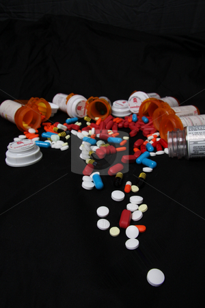 Pharmaceuticals  stock photo, Drugs, prescriptions medicines, pills, and bottles pouring out onto black background by JESSICA FELICIANA