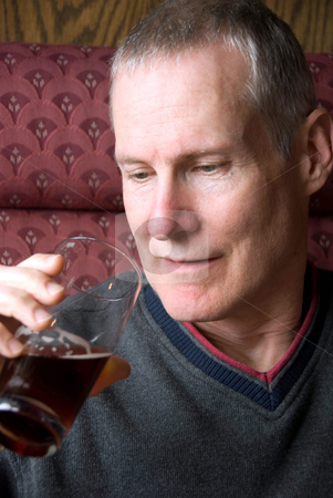 Man Drinking Beer stock photo, Stock photo of man in a restaurant about to take a sip from a glass of dark beer by Maria Bell