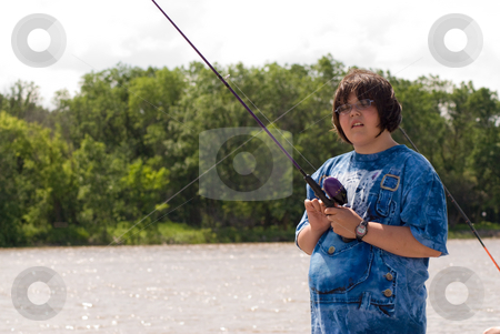 Young Girl Fishing stock photo, A young girl standing by a lake fishing during the day by Richard Nelson