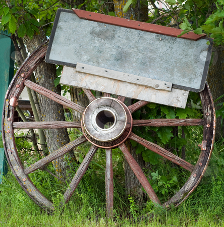 Wagon Wheel stock photo, Close-up view of a wagon wheel with a blank sign attached, perfect for your text by Richard Nelson
