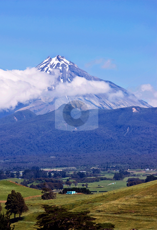 Taranaki stock photo, Mt Taranaki, a large dormant volcano rises steeply from the surrounding lush farmland by Robin Ducker