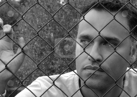 Man behind a fence stock photo, Man standing behind a fence in Black & White by Claudia Van Dijk