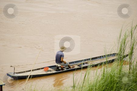 Man in boat stock photo, Man in boat in Luang Prabang with copyspace by Claudia Van Dijk