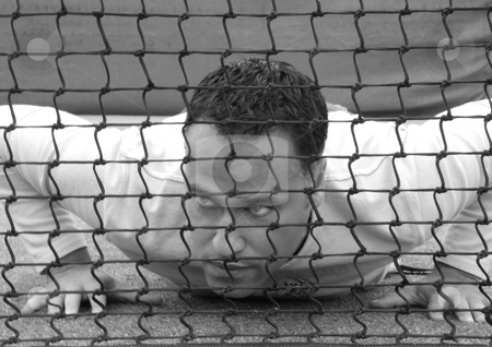 Man lying behind net stock photo, Man Lying on the ground behind a tennis net by Claudia Van Dijk