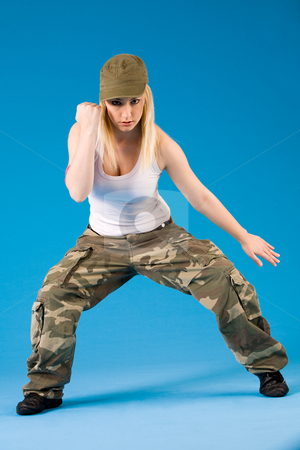 Blond sexy girl with dance moves stock photo, Attractive blond girl is dancing on a blue background by Frenk and Danielle Kaufmann