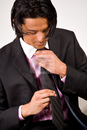 Young man bounding his necktie stock photo, Young indonesian man in a business suit by Frenk and Danielle Kaufmann