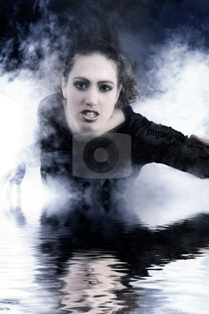 Woman with long curly hair crawling out of smoke stock photo, Portrait of a woman with long curly hair in smoke by Frenk and Danielle Kaufmann