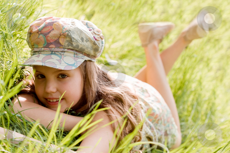 Relaxing young girl stock photo, Young girl is laying down in the grass by Frenk and Danielle Kaufmann