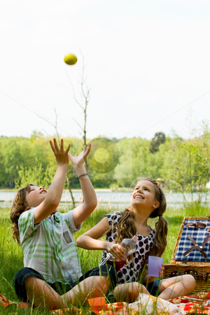 Throwing an apple stock photo, Two children enjoying a picnic in the summer by Frenk and Danielle Kaufmann
