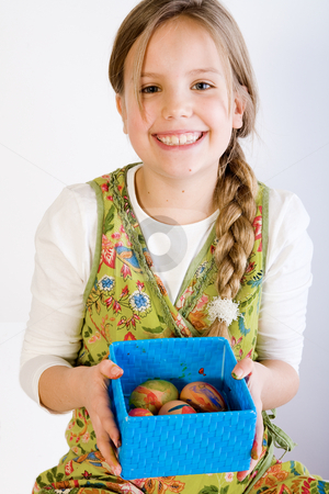 Young girl presenting a box with painted eggs stock photo, Studio portrait of a young blond girl who is presenting a blue box with her painted easter eggs by Frenk and Danielle Kaufmann