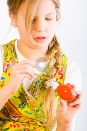 Young girl painting an easter egg red stock photo, Studio portrait of a young blond girl who is painting an egg red for easter by Frenk and Danielle Kaufmann