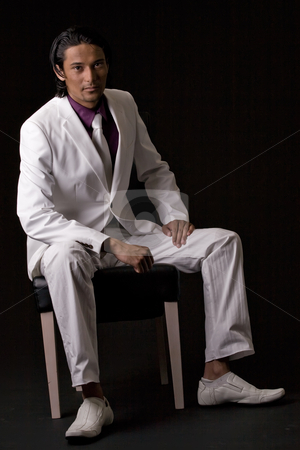 Business man sitting on a chair stock photo, Young indonesian man in a business suit by Frenk and Danielle Kaufmann