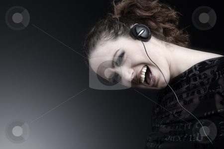 Woman with long curly hair enjoying nusic stock photo, Portrait of a woman with long curly hair and headphones by Frenk and Danielle Kaufmann