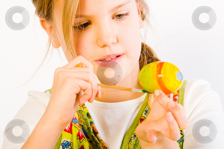 Young girl painting easter eggs stock photo, Studio portrait of a young blond girl who is painting eggs for easter by Frenk and Danielle Kaufmann