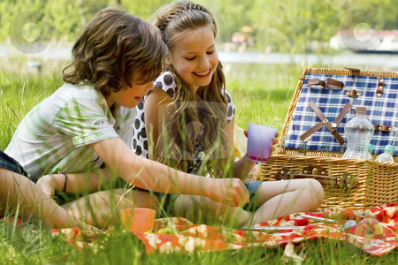 Kids having fun while picnicking stock photo, Two children enjoying a picnic in the summer by Frenk and Danielle Kaufmann