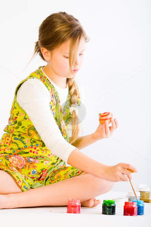Girl painting easter eggs stock photo, Studio portrait of a young blond girl painting eggs for easter by Frenk and Danielle Kaufmann
