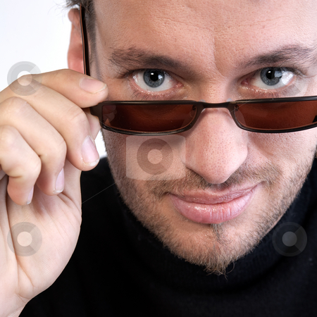 Portrait of a young adult man with sunglasses stock photo, Studio portrait of a young adult man looking over his sunglasses by Frenk and Danielle Kaufmann