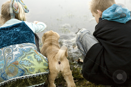 Water play stock photo, Brother and sister playing at the lake while sharpei puppy is watching by Frenk and Danielle Kaufmann