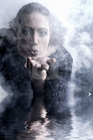 Woman with long curly hair blowing smoke stock photo, Portrait of a woman with long curly hair blowing by Frenk and Danielle Kaufmann