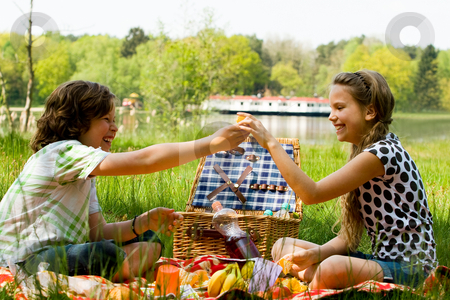 Share the orange stock photo, Two children enjoying a picnic in the summer by Frenk and Danielle Kaufmann