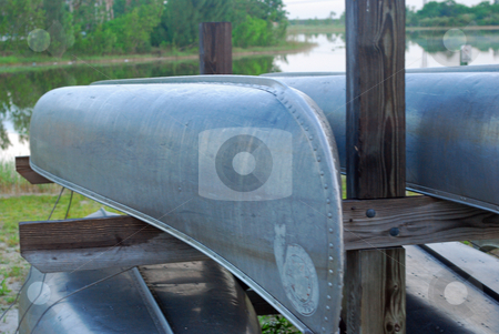 Canoes stock photo, Conoes stacked in a rack at a lake by Robert Cabrera