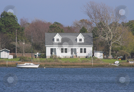 Seaside House and Sailboat stock photo, A house by the sea and a boat. by Robert Byron