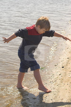 Boy Playing at the Ocean stock photo, A young boy playing at the seashore. by Robert Byron