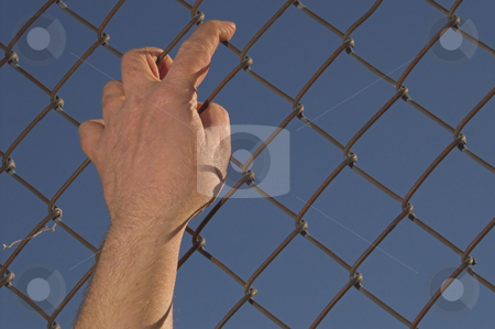 Escape stock photo, A person attempting an escape over a chain link fence. by Robert Byron