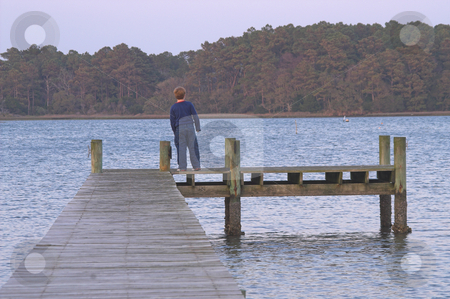 Boy on a Pier stock photo, A young boy standing on a pier. by Robert Byron