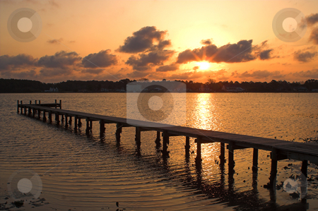 Sunrise or Sunset over a Pier stock photo, A sunrise or sunset over a pier of boat dock. by Robert Byron