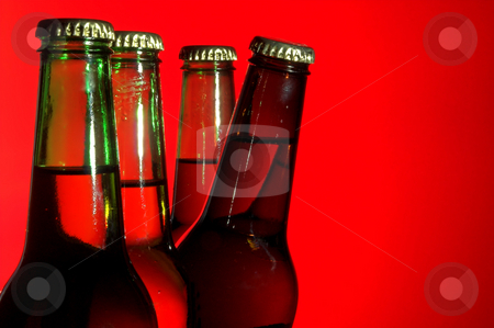 Peeking Beer stock photo, A delicious cold beer peeking from behind green bottles. by Robert Byron