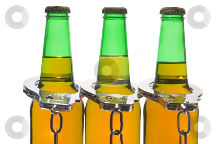 Beer and Handcuffs - Drunk Driving Concept  stock photo, Drunk driving concept - bottled beer and handcuffs. by Robert Byron