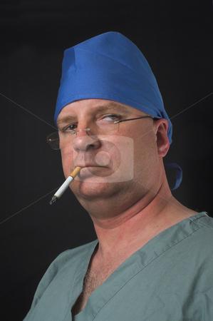 Surgeon General's Warning stock photo, A medical surgeon smoking an unhealthy cigarette. by Robert Byron