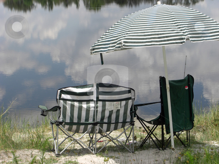 Empty chairs and umbrella stock photo, Empty lounge chairs and an umbrella are sitting at a lake with a reflection of the sky. by Rebecca Mosoetsa