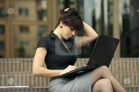 Busy lady with laptop stock photo, Busy young attractive lady playing with her hair and looking at a laptop on the stairs in front of an office building by Claudia Veja