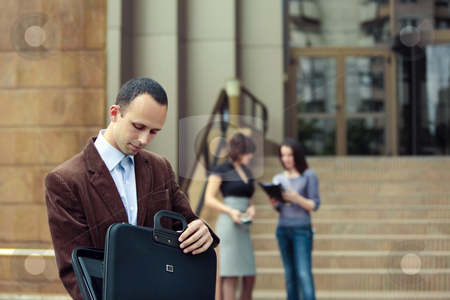 Business team outdoor stock photo, Business man looking in his briefcase and business ladies talking in the background in front of a building by Claudia Veja