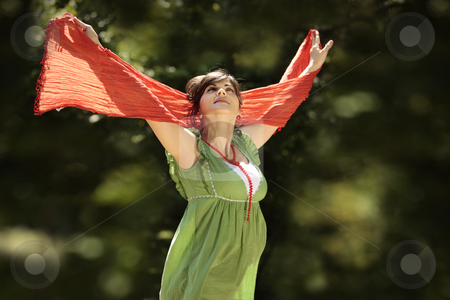 Woman catching wind stock photo, Young beautiful pregnant woman with the hands up in the air in nature by Claudia Veja