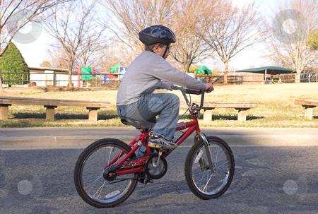 Boy Riding a Bike stock photo, A young boy riding his bike. by Robert Byron
