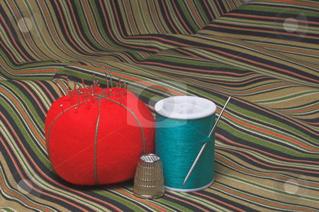 Sewing Supplies stock photo, A spool of thread, a thimble and a pin cushion. by Robert Byron