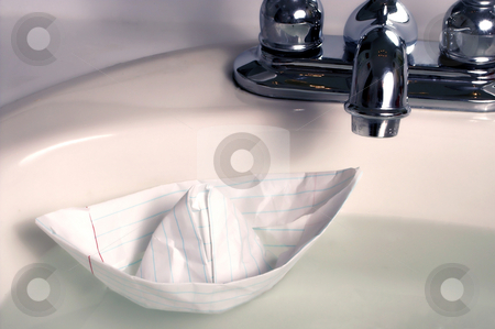 Paper Boat stock photo, A paper boat floating in a sink. by Robert Byron