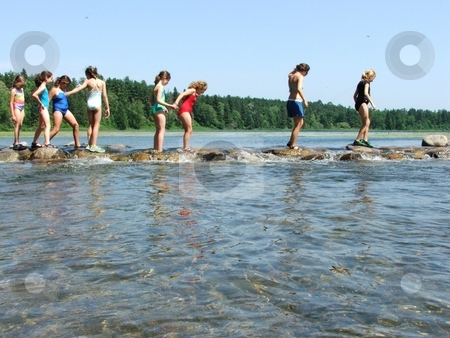 Girls Crossing the Mississippi stock photo, Young girls walk carefully over the slippery rocks at the source of the Mississippi River in Minnesota's Itasca State Park.  This spot, located in northern Minnesota, is a summertime favorite of kids and adults alike. by Dennis Thomsen