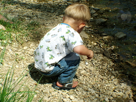 Picking up rocks stock photo, Young child picking up rocks by a creek by Michelle Bergkamp